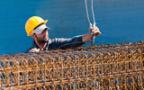Construction worker loading stack of reinforcement beam cages to poster