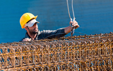 Construction worker loading stack of reinforcement beam cages to