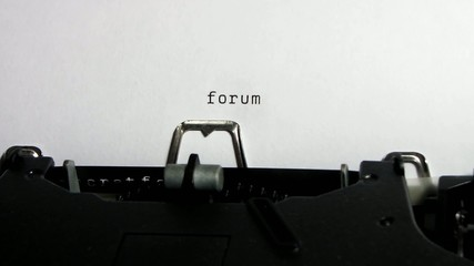 "Typewriter closeup writing ""forum"" on white paper"