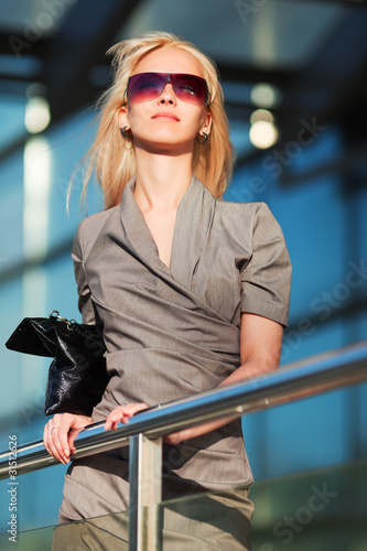 Young businesswoman against office windows