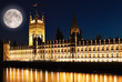 The Houses of Parliament in London with a bright  moon
