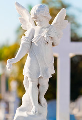 Child angel statue leaning in a cross on a cemetery