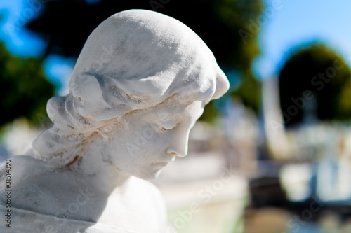 Statue of a woman's head with a diffused cemetery background