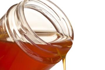 Jar spilling honey isolated on a white background