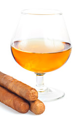 Glass of cognac  with a cuban cigar isolated on white
