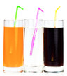 Three highball glasses of soda with drinking straws on a white b