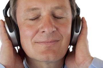 Attraktiver Rentner mit Kopfhörer hört MP3 Musik und genießt