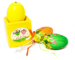 yellow easter candle and decorative eggs isolated on white