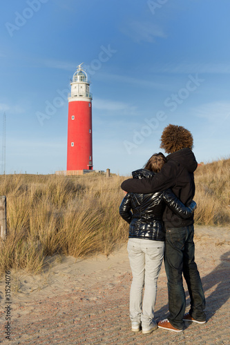 Couple in love near red lighthouse