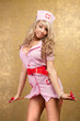 sexy blonde woman in seductive pink nurse costume on golden back