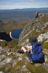 Backpacker looking down at Lake Rhona, Tasmania, Australia.