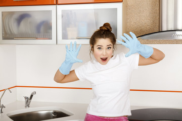 Young woman in blue rubber gloves in the kitchen