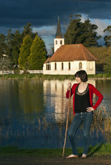 Woman leaning on stick by church