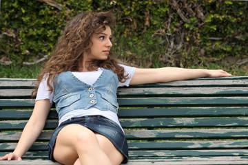 ragazza seduta su panchina di legno