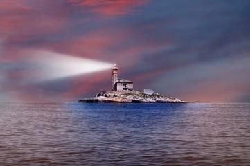 Light lighthouse in the dusk at sunset