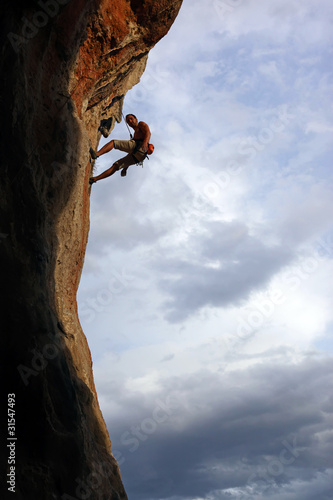 Silhouette of rock climber against cloudy sky