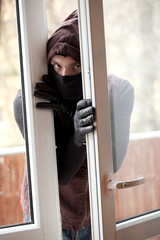 burglar in mask and hood breaking into house through window