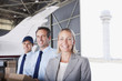 Businesswoman and workers standing in hangar
