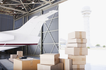 Boxes stacked near airplane in shipping area