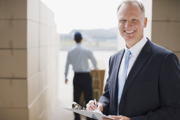 Supervisor holding clipboard in shipping area