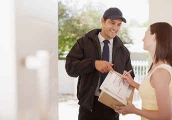 Woman signing box receipt for delivery man