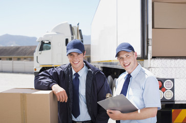 Workers standing with boxes near semi-truck