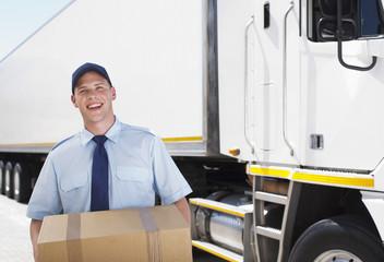 Worker carrying box near semi-truck