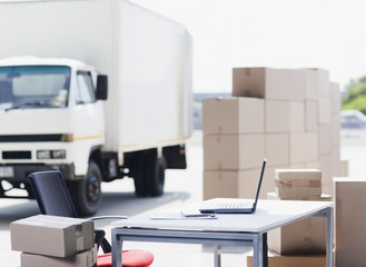 """Truck, boxes, desk and laptop in shipping area"""