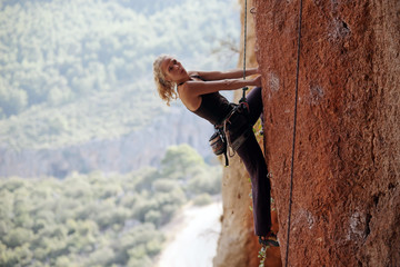 Female climber preparing to the next move on her way up
