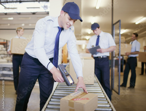 Worker scanning box on conveyor belt in shipping area