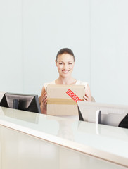 Receptionist holding box marked urgent