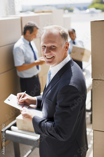 Supervisor writing on clipboard in shipping area