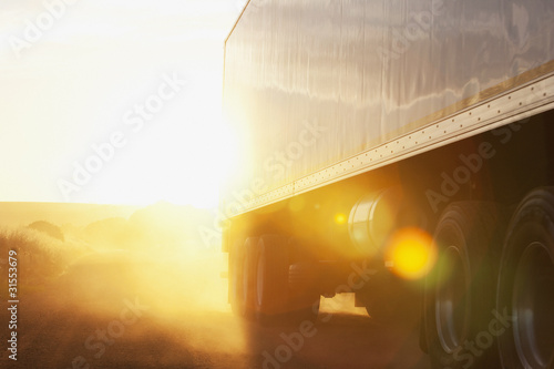 Semi-truck driving on dirt road