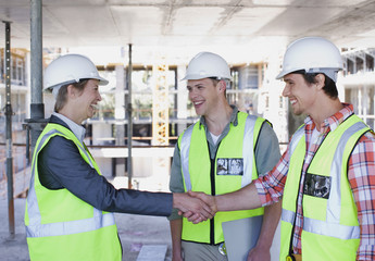 Construction worker shaking hands on construction site