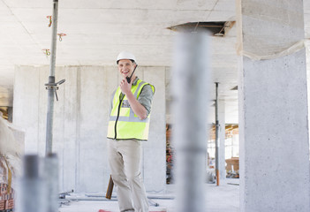 Construction worker talking on walkie talkie on construction site