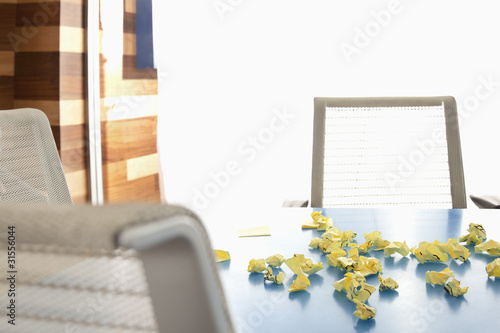Crumpled adhesive notes on conference room table