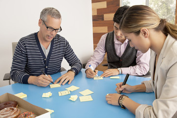Business people writing on adhesive notes in conference room