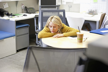 Businesswoman sleeping at desk in office