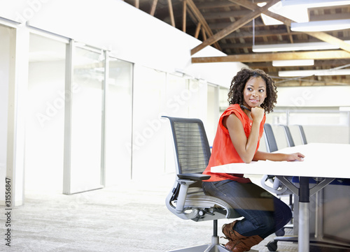 Businesswoman sitting alone in conference room