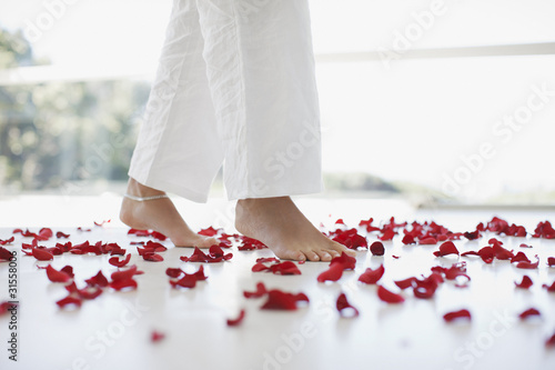 Woman walking through flower petals on floor