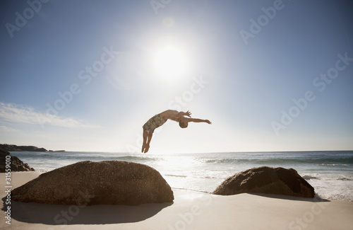 Man doing backflip on beach