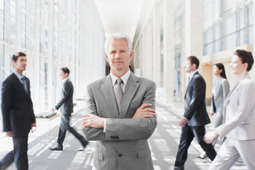 Busy co-workers walking past businessman
