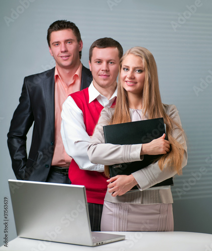 Two men and woman working with a computer