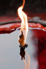 Close up of a red burning candle