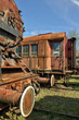 Corroded steam locomotive and railcar at train graveyard