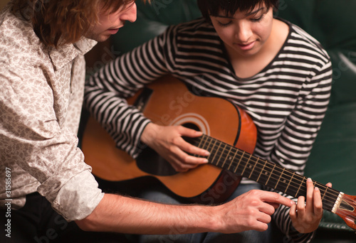 Young Musician Teaches Female Student To Play the Guitar - 31585697