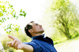 Satisfied smiling businessman standing in the green outdoors.