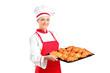 A female baker holding freshly baked croissants