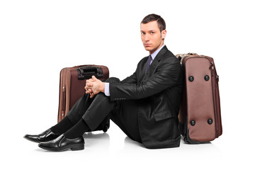 A business traveler waiting seated next to suitcases