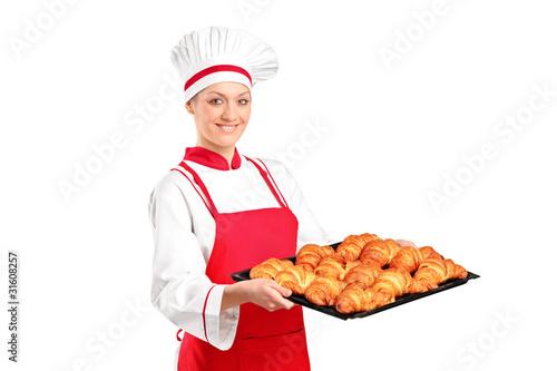 A female baker holding freshly baked croissants - 31608257